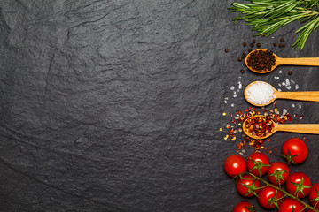 Colorful spices in spoons and tomatoes on dark vintage background. Top view. Food and cuisine ingredients.