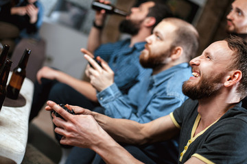 A company of four men with a beard sitting on the couch at home with beer and chips, two of them with joysticks in hand playing computer video games, the other carefully watching the game.