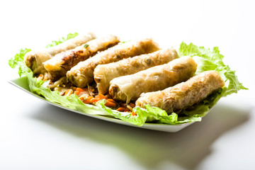 Spring rolls surrounded by vegetables