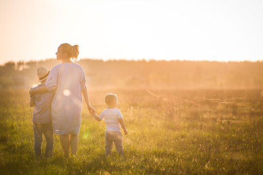 Beautiful young woman with two boys on the daisy meadow on a sunny day. Happy family on summer sunset. Kid boy, toddler and mom. Mum with baby and kid. Family and lifestyle concept