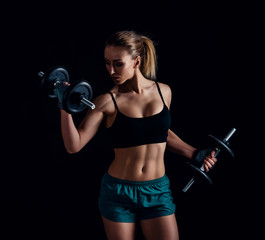 Portrait of a young fitness woman in sportswear doing workout with dumbbells on black background. Tanned sexy athletic girl. A great sporty female body.