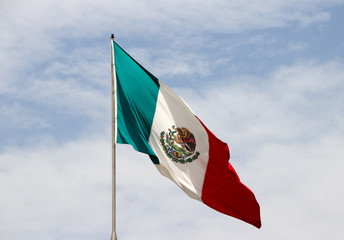 Mexican flag and blue cloudy sky