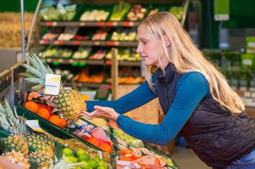 Junge Frau kauft im Biomarkt eine Ananas