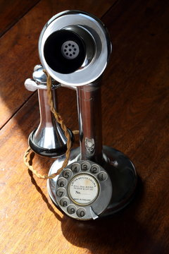 Retro chrome candlestick telephone on wooden desk