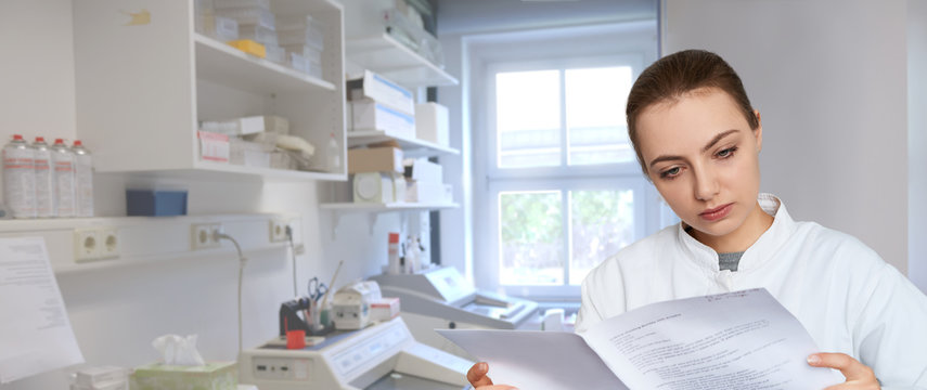 Young female scientist reading printed notes in scientific laboratory, panoramic image