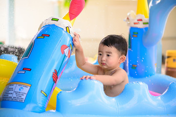 Sad Asian kid playing alone in inflatable baby pool..