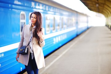Young elegant girl in a stylish coat standing on a railway platform near the train before boarding.