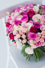 Large  bouquet of roses on  white chair.