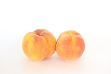 Two fresh whole peaches, isolated on white
