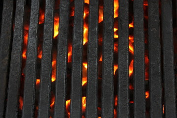 Close-up BBQ grates over blazing charcoal