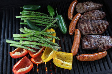 Veggies, sausage and steaks on a charcoal BBQ