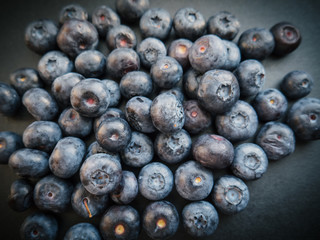 Natural looking blueberries on dark background. Top view. Selective focus in the middle.