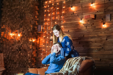 A loving couple in a loft-house with a textured wooden wall and lights. A pleasant home environment with a leather sofa and an armchair in the evening for lovers.