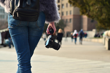 Rear view of a female photographer with a black modern digital photocamera in her hand against a blurred background of crowded street with many people