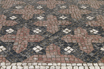 Texture of an unusual pattern laid out from the tile on the streets of the city.