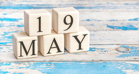 May 19th. Wooden cubes with date of 19 May on old blue wooden background.