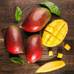 Slised ripe mango on wooded board.