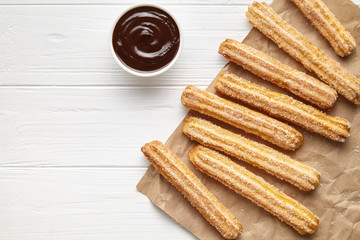 Churros traditional Spain street fast food baked sweet dough snack with chocolate, rustic decorative paper, white table background. Flat lay top view