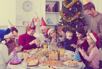 Large family making numerous photos during Christmas dinner