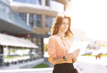 Portrait of pretty businesswoman smart casual using digital tablet outdoors