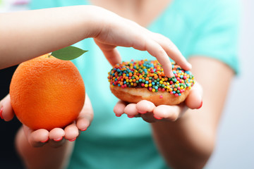 Child obesity concept with little girl hand choosing a sweet and unhealthy doughnut instead of a fruit