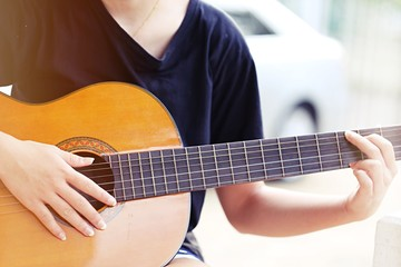 Young teenage girl playing ukulele music instruments sitting relax outdoor background