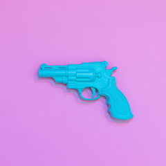 Blue painted gun in Double Exposure. Minimal flat lay.