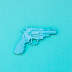 plastic gun painted blue. minimal flat lay.