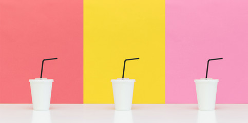 three white paper cups with drinking straws on different backgrounds.