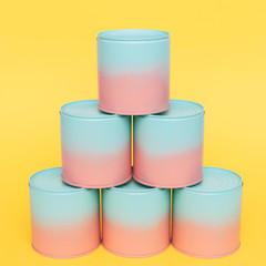 six painted jars with dip-dyed pink and blue colors stand like pyramid on yellow background