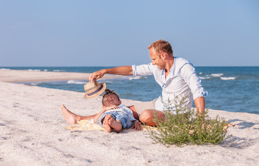 Father with son spent time together on the sea sand beach in sunny day