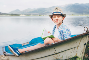Boy with book sits in old boat on the mountain lake bank