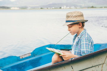 Boy reads a book in old boat on the lake bank