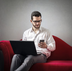 Man using smartphone and laptop at the same time