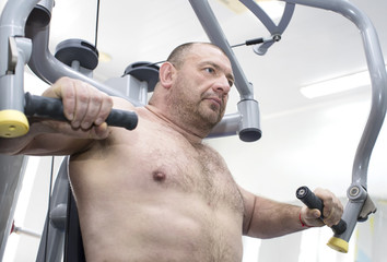 The adult brutal man is engaged in power bodybuilding in the gym
