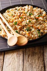 Fried Thai rice with minced meat and carrots close-up. vertical