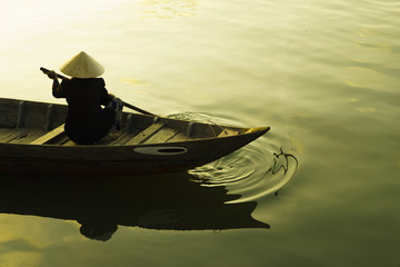 Vietnamese woman rowing boat on river