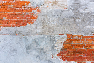Old brick wall texture, covered with multiply stucco plaster layers, weathered and distressed