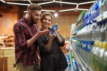 Happy loving couple in supermarket choosing water.