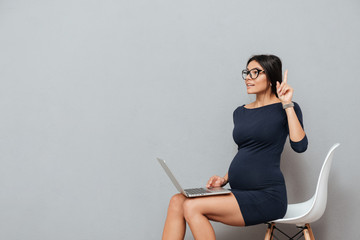 Beautiful pregnant business woman have an idea using laptop