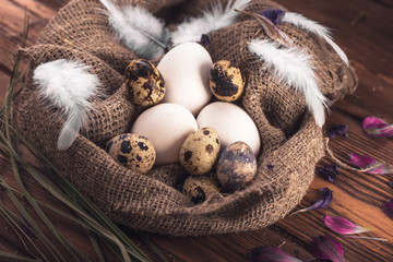 Chicken and quail eggs in the sackcloth on a wooden background. Close-up.