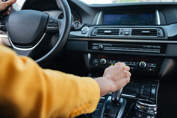 Hand of female driver shifting gear stick before driving car