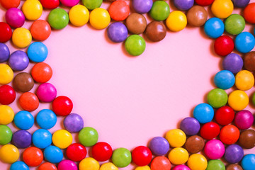 Frame of heart form of multi-colored candies on pink background