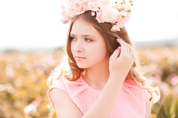 Summer portrait of teen girl 14-16 year old wearing floral wreath with roses outdoors. Standing in rose field. Looking away.