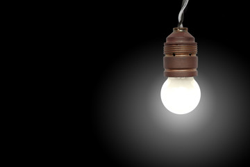 Eine hängende Glühbirne, Licht an, vor schwarzem Hintergrund