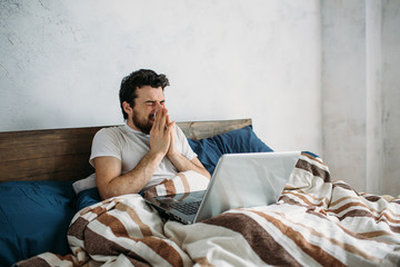 Bearded man lying in morning bed with laptop