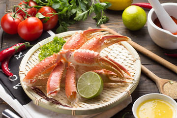 Boiled crab claws with spices and sauce on a white plate and wooden background