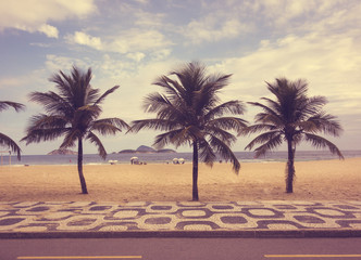 Ipanema beach with palms and mosaic of sidewalk in Rio de Janeiro, Brazil. Vintage toning