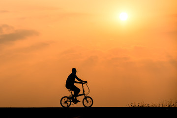 Silhouette of cyclist on sunset background