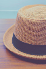 fedora hat over wooden table with sea background.